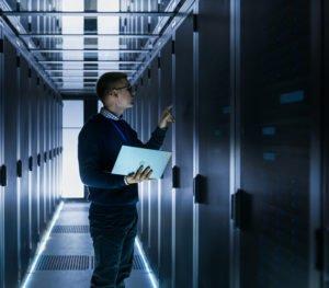 Mann mit Notebook im Serverraum